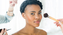 This bronzed beauty look features gold lids, happy cheeks and a graphic braid updo. The color palette remains neutral, while the updo gives a fresh take on the traditional braid. Remember to start with moisturized skin, and to use appropriate brushes for each step—stiffer brushes applies more pigment, softer ones apply less.