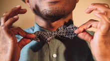 No longer a fixture just for tuxedos, bow ties have a look of old world grandeur and modern sophistication. And who better to teach us the gentleman sport of tying a bow tie than Augustine B. Emuwa, Owner and Lead Craftsman of Knits&Knotts. Augustine credits his father and grandfather as style inspiration for Knits&Knotts to create modern classics. Ditch the clip on to get all tied up and spiffy in 10 steps with this bow tie how-to.